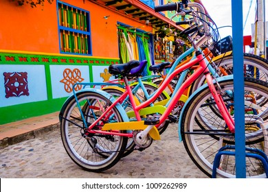 GUATAPE, COLOMBIA - OCTOBER 19, 2017: Close up of bikes parked in a row in a beautiful colorful streets and decorated houses of Guatape city near Medellin, Antioquia, Colombia