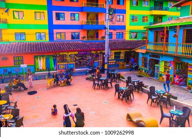 GUATAPE, COLOMBIA - OCTOBER 19, 2017: Unidentified people sitting in the square surrounding of decorated buildings of Guatape city near Medellin, Antioquia, Colombia