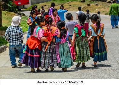 Guatemala - 04-21-2014: Group of Guatemalan school children walk on road, holding hands, when one little girl whispers in a friend's ear.