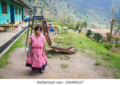 Guatemala - 04-21-2014: A Guatemalan girl in ethic dress stands in front of a broken slide on the playground at a poor rural school.