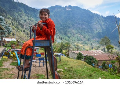 Guatemala - 04-21-2014: Smiling young student sits atop a broken metal slide at a rural Guatemalan school where all the villagers live in poverty.