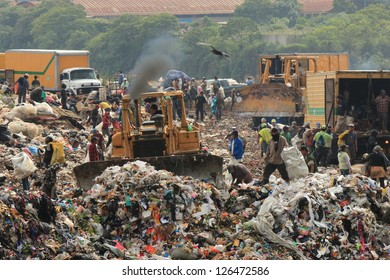 GUATEMALA CITY - AUGUST 7: Employees and Scavengers are processing waste in Landfill at Guatemala City on August 7, 2012. People searching for refuse to recycle or resell.