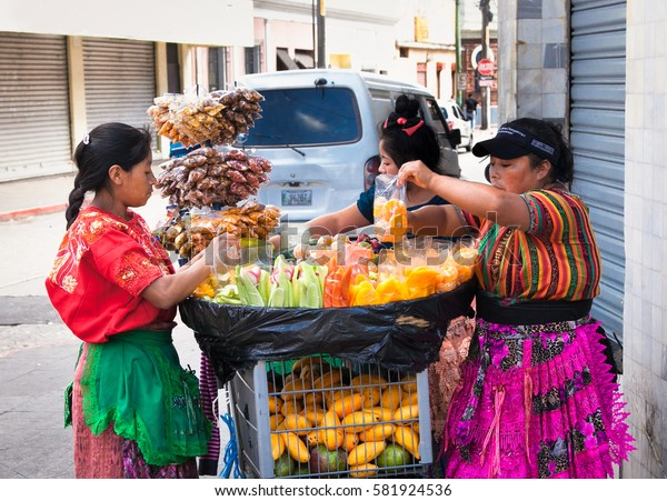 GUATEMALA CITY, GUATEMALA-DEC 25, 2015: Mayan women sell   Guatemalan food and fruits at the street of Guatemala city on Dec 25 2015. Guatemala.