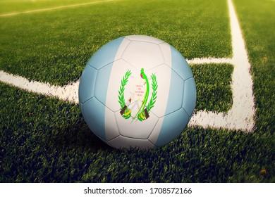 Guatemala flag on ball at corner kick position, soccer field background. National football theme on green grass.