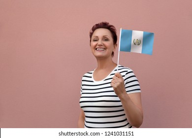 Guatemala flag. Woman holding Guatemala flag. Nice portrait of middle aged lady 40 50 years old with a national flag over pink wall background outdoors.