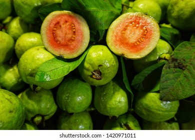Guava is an edible light green fruit with pink and white flesh, round or pear-shaped and hard seeds, juicy flesh and a strong, sweet aroma. Selective focus.
