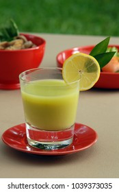 Guava juice on red dish and decorated with slice lemon and leaf.