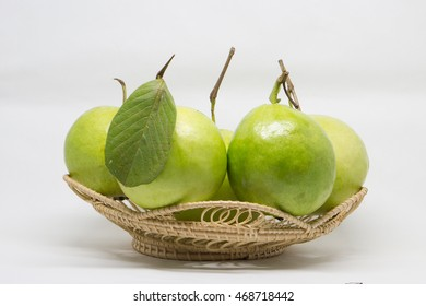 Guava (tropical fruit) in wicker basket on the white background