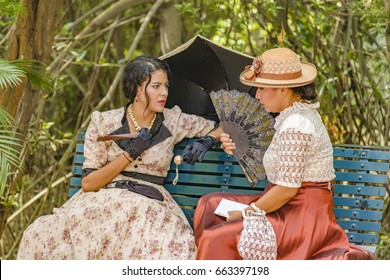 GUAYAQUIL, ECUADOR, MAY - 2016 - Two adult young actresses with 19th century clothes chatting at historic park located at samborondon neighborhood, Guayaquil, Ecuador