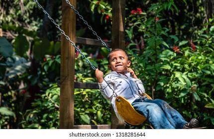 Guazacapan Guatemala 02/10/2019 young latin boy playing on swing in Guatemalan playground