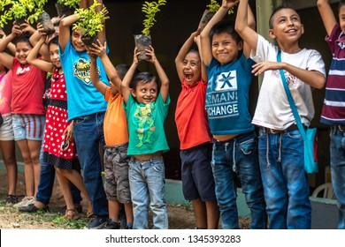 Guazacapan Guatemala 03/20/2019 latin children holding plants in Guatemala