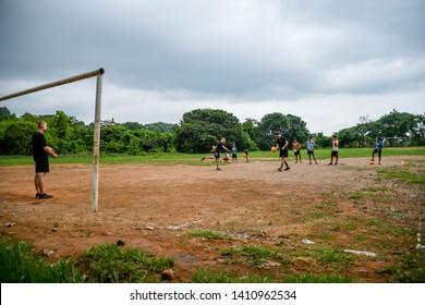 Guazacapan Guatemala 05-15-2019 caucasian man teaching soccer football to latin children in Guatemalan village