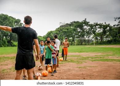 Guazacapan Guatemala 05-15-2019 caucasian man teaching soccer football to children in Guatemalan village