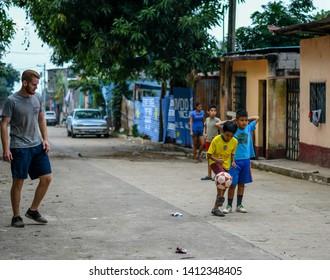 Guazacapan Guatemala 05-15-2019 caucasian men playing soccer football with  latin children in Guatemalan village
