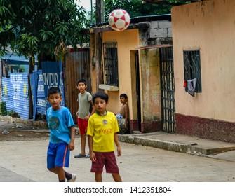 Guazacapan Guatemala 05-15-2019 latin children playing soccer football in streets in Guatemalan village