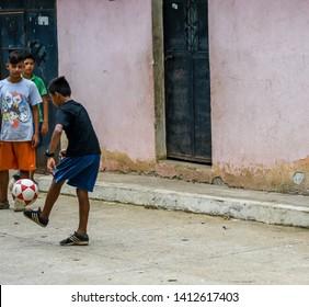 Guazacapan Guatemala 05-15-2019 latin children playing soccer football in Guatemalan streets