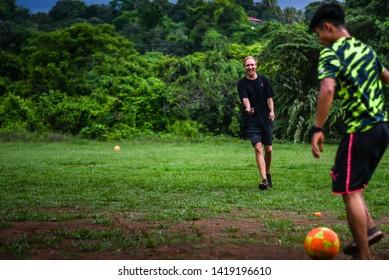 Guazacapan Guatemala 05-20-2019 caucasian coach's playing soccer/football with latin children in Guatemalan village