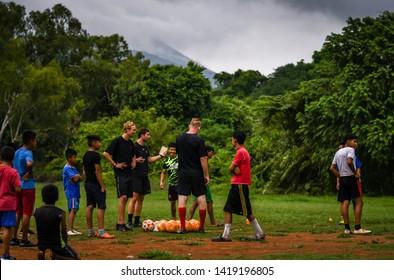 Guazacapan Guatemala 05-20-2019 caucasian coach's teaching soccer/football to latin children in Guatemalan village
