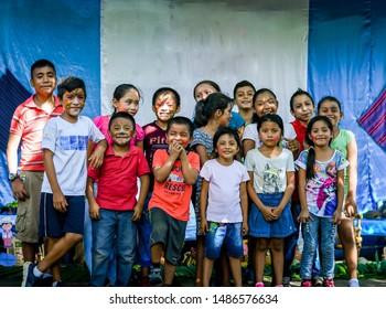 Guazacapan Guatemala 08/23/2019 latin children in front of Guatemalan flag smiling