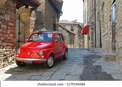 Gubbio, Italy - August 24, 2018: Old red Fiat 500 in narrow street of the town