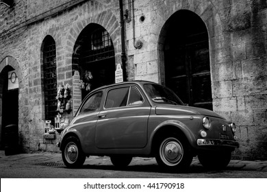 GUBBIO, ITALY - MAY 13;Gritty monochrome image in traditional back Italian street with iconic small car surrounded by old stone buildings vignette May 13, 2011 in Gubbio Italy