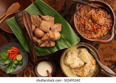 Gudeg Jogja. A signature dish from Jogjakarta. Shown here each individual dish that makes up the complete gudeg meal. Served in earthenware serving dish; arranged on a table covered with batik cloth.