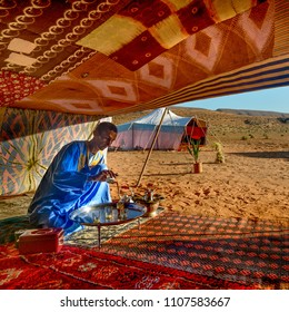 GUELMIM , MOROCCO - OCTOBER 30, 2015: Berber man preparing tea for guests at a camp near Guelmim in the Sahara desert , Morocco.