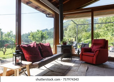 GUERNICA, BIZKAIA BASQUE COUNTRY MAY 22 2017: nice and warm living room with red sofas and a fireplace of a small rural hotel in the Basque mountains near Bilbao