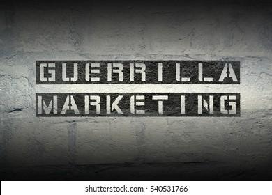 guerrilla marketing stencil print on the grunge white brick wall