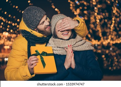 Guess who? Photo of two people couple guy closing eyes lady waiting surprise holding her x-mas giftbox wear jackets caps scarfs newyear spirits atmosphere park outside