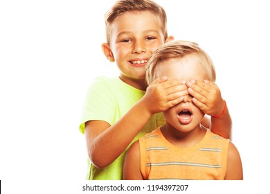 Guess Who, See no evil concept. Two funny siblings brothers playing hide-and-seek game: elder boy embraces face of his little friend. Yonger boy is frightened. Copy-space. Studio shot
