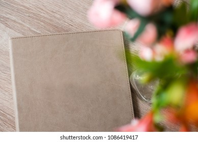 Guest book or menu of the hotel in composition with flowers. Top view. Free space for text