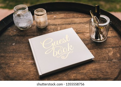 Guest book for wedding remembers and glass jars with pens on a wooden barrel