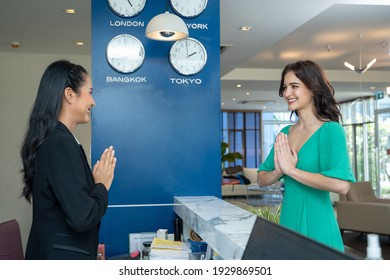 Guest checking in at counter with reception at hotel.