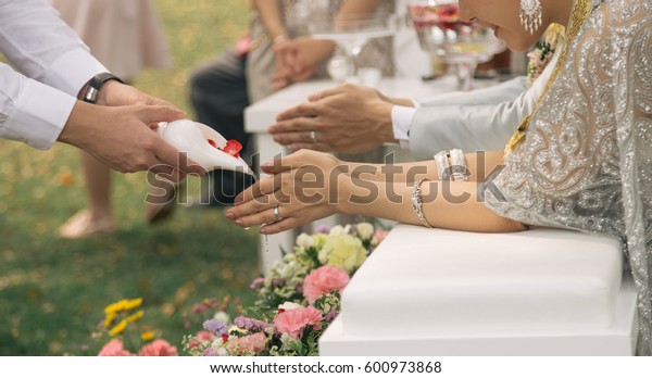 Guest Pouring Holy Water from Conch Shell to Bless Couple in Thai Wedding