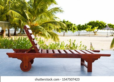Сomfortable guest sun lounger and a bedside table are worth on a wooden platform. Great review for a luxury beachfront pool, the ocean and swaying palm trees. Charming lookout