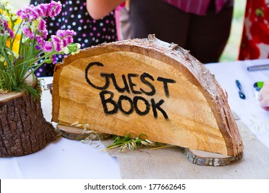 Guestbook sign is made from a crosscut section of a fir tree with the letters guest book burned into the wood grain at a wedding ceremony.