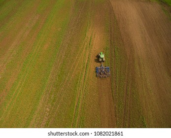 Guestrow, Germany - May 02. 2018: aerial view of a modern John Deere tractor pulls a plow trailer. The farmer plows with a modern John Deere tractor in an agricultural field in spring