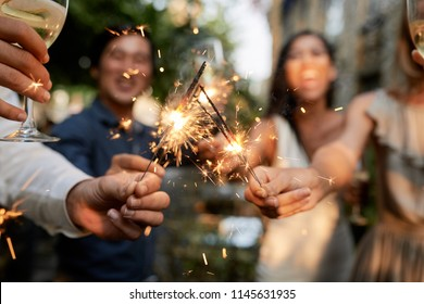 Guests burning sparklers and having fun at big outdoor party