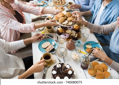 Guests by festive table helping themselves with fresh homemade pastry