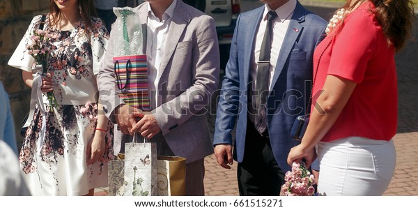 guests congratulating newlywed couple with presents at reception, people holding gifts for bride and groom