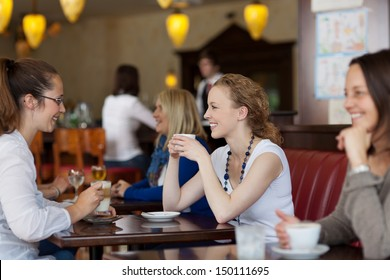 Guests enjoying coffee in a restaurant with focus to two stylish young woman sitting at a table together