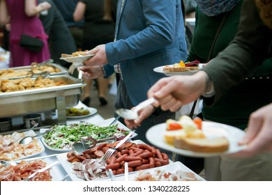 Guests of a festive event enjoying catering.