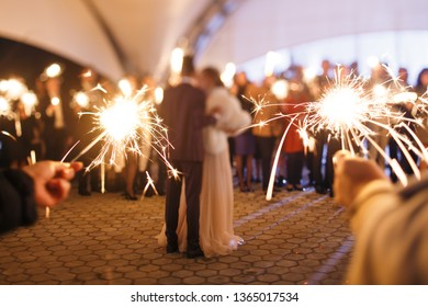 The guests and the newlyweds lit sparklers at the end of a wedding in the evening on the street. No faces