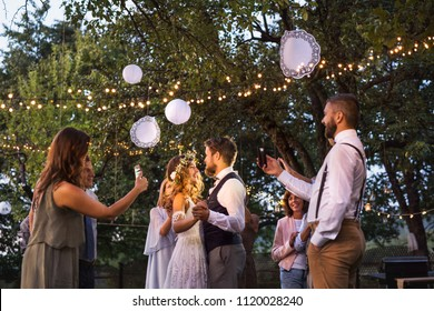Guests with smartphones taking photo of bride and groom at wedding reception outside.
