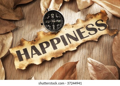 Guidance and key to happiness concept using printed word on burnt paper along with compass, surrounded by dry leaf