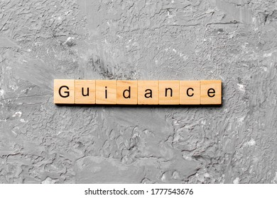 Guidance word written on wood block. Guidance text on table, concept.
