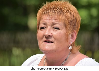 A guide in Belovezhskaya Pushcha on the Museum of Life Redhead The elderly woman with a short haircut with ornaments looks far into the editorial July 2017 Belovezhskaya Pushcha Belarus
