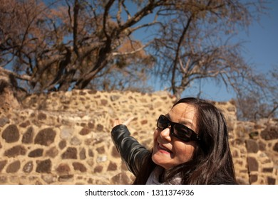 Guide woman who smiling works explains and points out vestiges in archaeological zone dating from the year 1153 in the pyramid buried in the chasm of the great hill of the speaker in a state of Mexico