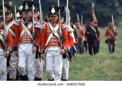 Guildford Surrey UK 1996. Re-enactors of the Napoleonic Wars march through a field in the period uniform of British Fusiliers followed by Flag bearers at a re-enactment of the Battle of Waterloo 1815.